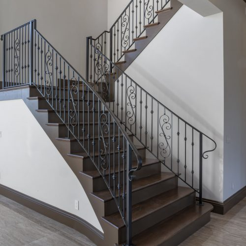 ornate staircase at new custom lakefront home